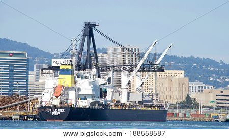 Oakland CA - May 28 2017: Bulk carrier NEW LEADER loading at Schnitzer Steel at the Port of Oakland. Schnitzer Steel recycles scrap metal into finished steel products such as rebar and wire rod.