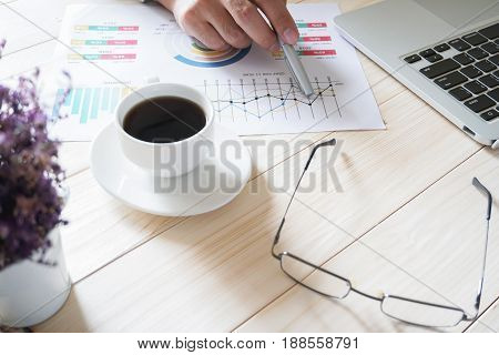 businessman hand working on wooden desk in office and there are many documents graphs. Can be attributed to financial articles.