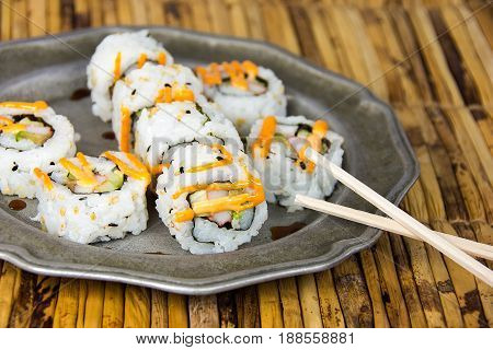sushi pinwheel and wooden chopstick on pewter plate and bamboo place mat