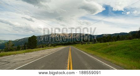 A well worn two lane road leads to a vanishing point in the mountains