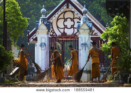 AYUTHAYA THAILAND - MARCH 28 2015 : thai younger monk of wat niwat thumaprawat temple morning daily cleaning sweeping dry leaves on walking path way of temple entrance