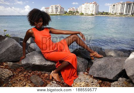 Attractive black model in an orange jumpsuit