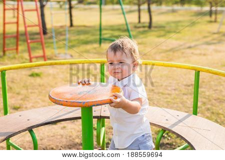 Cute young child boy or kid playing on playground