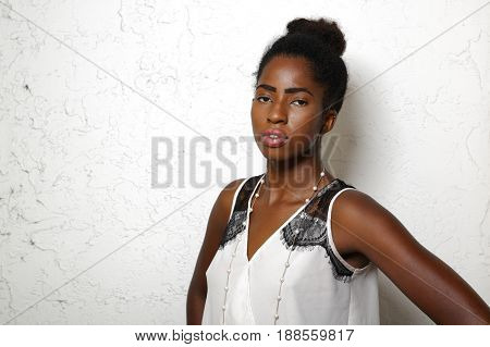 Upper body photo of a young black woman with a hair bun posing on a white background