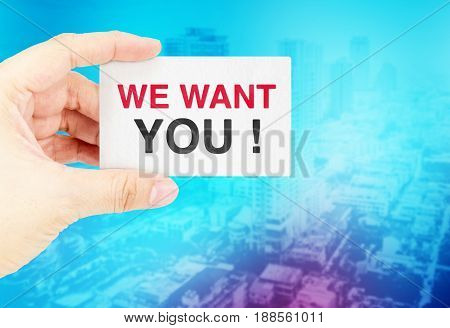 Hand holding Business card with We want you with blur blue bokeh backgroundBusiness concept.