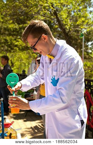 Khabarovsk Russia - May 20 2017: Young smart professor carrying out an experiment at science show for kids. Fun chemistry laboratory for children - a teacher mixing liquids in a glass