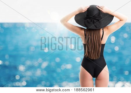 Woman with elegant black swimsuit and straw hat watches the sea