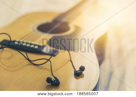listening and play the music with guitar relax happy time with song concept. closeup wood folk guitar with earplug headphone vintage color tone.