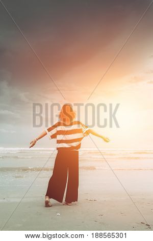 Women freedom single travel concept. Girl free emotion body language at the strom sea beach with sun light vintage color tone.