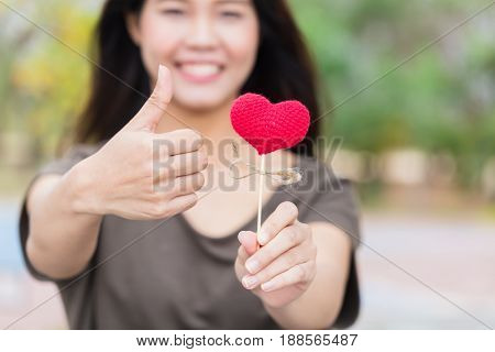 Good Heart Medical Care Concept, Smile Asian Teen Thumb Up Hand Holding Red Heart.