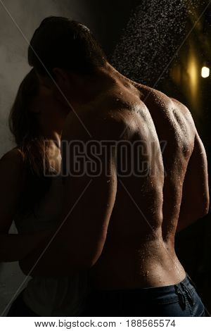 Gorgeous couple nude embracing in dark studio aqua zone