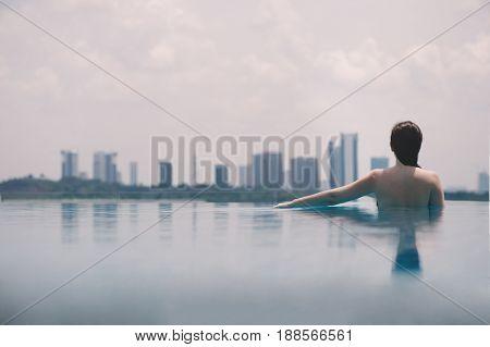 Beautiful girl in the pool on the background of the city of Malaysia Putrajaya. Putrajaya Skyscrapers