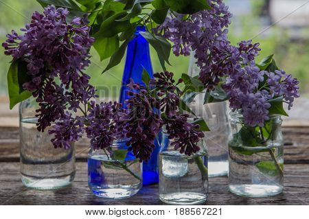 Lilac Flowers In Jars And Bottles On The Wooden Window Sill
