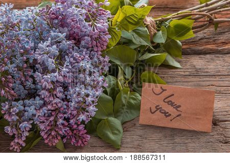 Lilac Flowers Bouquet And Craft Paper With Text I Love You On The Old Wooden Background