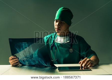 Male doctor or surgeon looking at mammogram xray film while using tablet computer in a dark room. Mystic and vintage look. Medical and doctor concept.