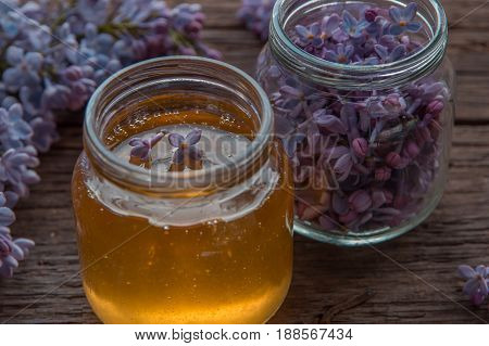 Honey And Lilac Flowers In Glass Jars On Wooden Background