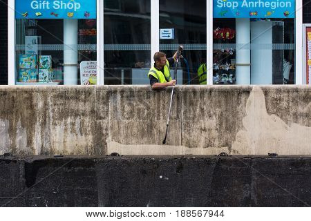 CARDIFF UK - MAY 29 2017 Workman using pressure jet to clean wall. Man uses pressure washer to remove dirt from concrete surrounding Mermaid Key