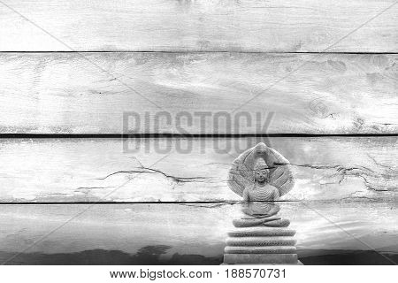 Black and white view Overlay the outdoor beautiful stone Buddha Image covered with seven heads of Naka (Great Snake) on Told wood texture.