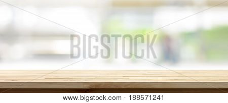 Wood table top on blur white green kitchen window background panoramic banner - can be used for display or montage your products (foods)