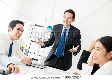 Happy cheerful businessman as a meeting leader talking to his colleagues in the meeting