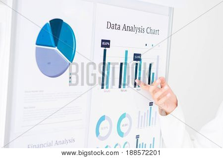 Businesswoman hand pointing at the graph on the board presenting and analyzing information