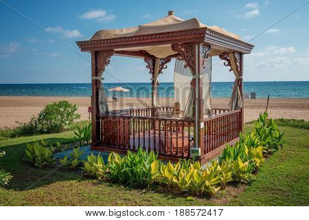 A cozy wooden sea bower on the beach.