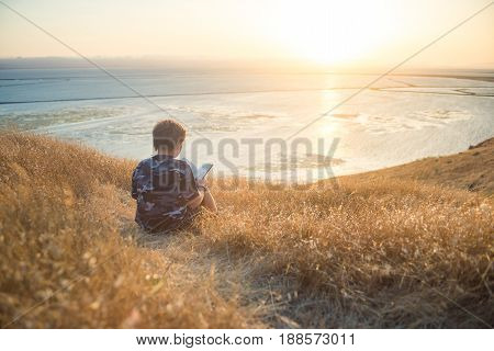 Boy reading book in yellow grass high in the hills, watching beautiful sunset above Bay Area, rear view. Can be used as header.