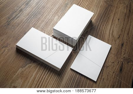 Photo of business cards on wooden office table background. Stacks of business cards. Template for branding identity.