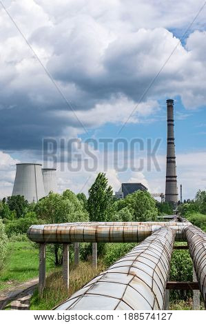 Hot water and central heating pipelines with a cogeneration plant on the background outside of the city