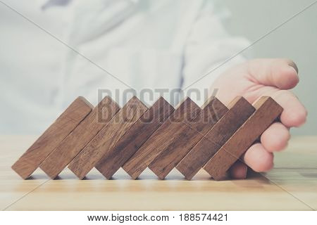 Businessman hand support wood block domino effect Business risk management concept