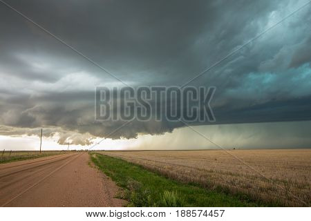 A wall cloud forms underneath a tornadic supercell thunderstorm as it gathers strength.