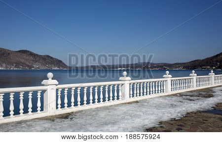Quay by the lake Baical. Winter landscape view. Snow-covered shore of the lake