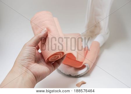 isolated close up nurse hand with bandage for wrapping splint to wound treatment