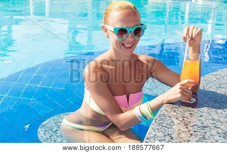 Girl in pool bar at tropical tourist resort vacation destination