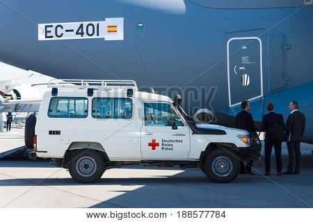BERLIN GERMANY - MAY 21 2014: A car with the humanitarian aid of the German Red Cross prepares for loading into military transport aircraft Airbus A400M Atlas. Exhibition ILA Berlin Air Show 2014