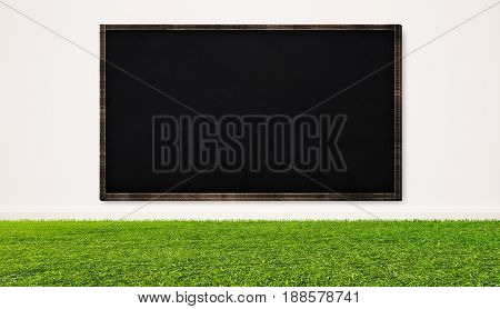 Blackboard on white wall with grass lawn