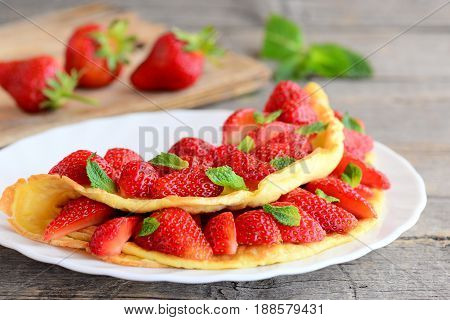 Delicious strawberry omelette. Omelette stuffed with strawberries slices and garnished with mint leaves on a plate. Fresh strawberries on wooden table. Breakfast or brunch menu. Rustic stile. Closeup