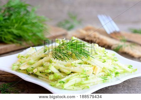 Zucchini cheese salad. Salad with fresh zucchini slices, cheese slices and chopped dill on a plate. Simple and quick vegetarian summer salad. Rustic style. Closeup