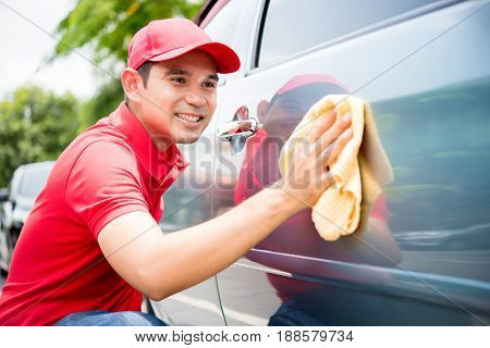 A man in red uniform cleaning car - auto cleaning service concept