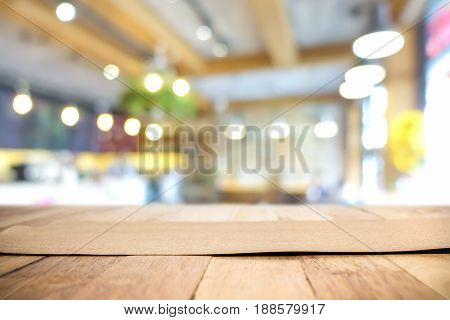 Brown paper on wood table top in blur cafe interior background - can be used for montage foods or products