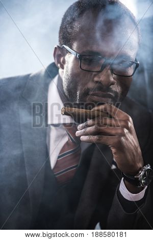 portrait of confident african american businessman smoking cigar