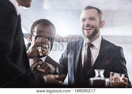 Multiethnic Group Of Businessmen Spending Time Together Drinking Whiskey And Smoking, Multicultural