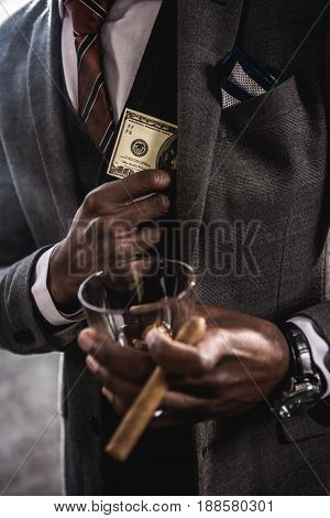 Close-up partial view of african american businessman holding glass of alcohol beverage and cigar while hiding dollar banknote in suit jacket pocket
