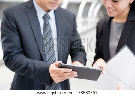 Businesswoman and businessman looking at tablet pc