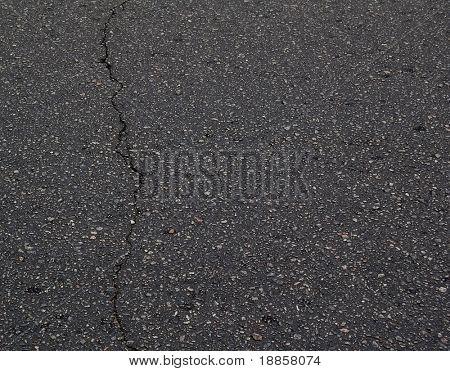 Old Black Asphalt Texture with a Crack. Asphalt Background with Space for Text.
