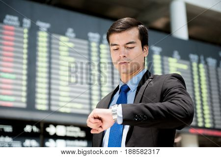 Businessman looking at his watch in front of airport timetable at the airport terminal