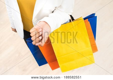 Woman arm carrying colorful paper shopping bags
