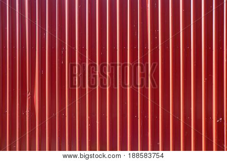 Red long goffered metal texture, corrugated steel surface. Industrial background.