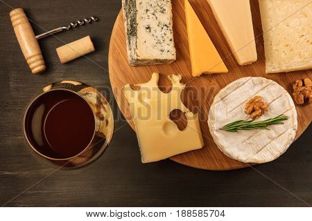 An overhead photo of a selection of cheeses, shot from above on a black texture, with a wine corkscrew, a cork, and a glass of red wine, with a place for text