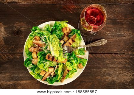An overhead photo of a plate of chicken Caesar salad with a fork and a glass of rose wine, on a dark rustic background with a place for text